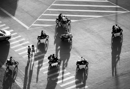 Amazing scene on street at Asian city from high view, group of Vietnamese people circulation by motorcycle, car or walking with shadow on road surface make impression overview