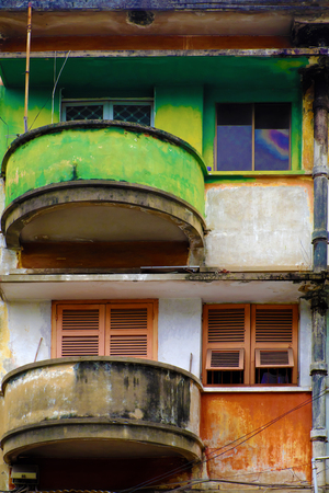 Amazing facade building with contrast color is green and red, antique flat with old architecture at Ho Chi Minh city, Vietnam, vintage wooden window and balcony round from house 写真素材