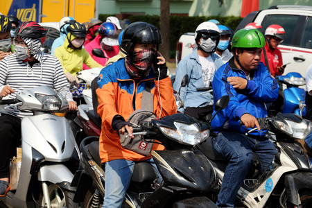 HO CHI MINH CITY, VIET NAM- APRIL 26, 2019: Group of Vietnamese wear glasses, face mask ride motorbike under high temperature in hot day, tired face in extreme weather