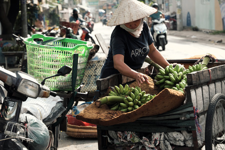 HO CHI MINH CITY, VIET NAM- JULY 06, 2019: Vietnamese woman transport many banana bunch by cart, female stand consider on bananas at roadside, close up scene with blurred background on day