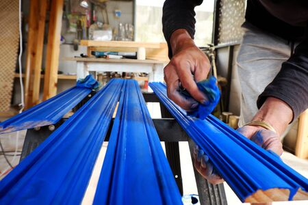 Vietnamese man working in workshop, male hands painting on wooden bar with blue paint coating, people do it yourself furniture for home at Da Lat, Viet Nam