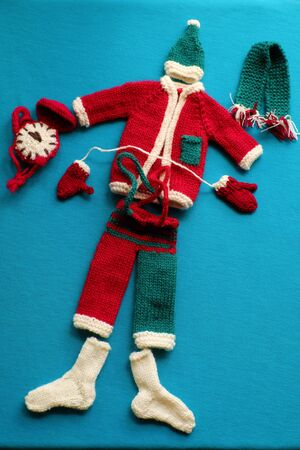 Top view of Santa clothes with accessories as gloves, hat, scarf, socks in white, red and green knit from yarn on blue background, small decorations for Christmas season at winter holiday