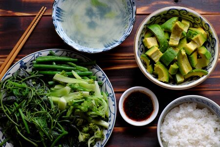Top view Vietnamese vegetarian meal, boiled vegetables with string bean, broccoli, sweet potato buds, avocado salad with soy sauce and rice, a diet non meat only vegetables that frugal
