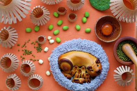 Top view of moon cake with mother pig and piglets shape, baking materials, paper lanterns, traditional baked pastry for mid autumn season on orange background