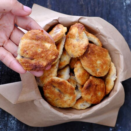 Close up woman hand pick a pastry, homemade cake for snack, coconut cassava pies baked on burlap background.