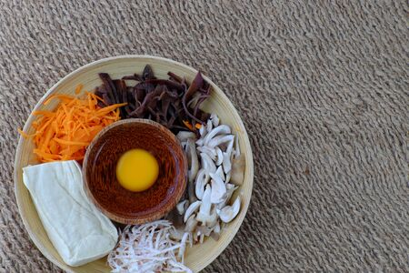 Top view homemade food on burlap background, raw materials for vegetarian dish from mushroom, tofu, carrot, egg, vegan sausage