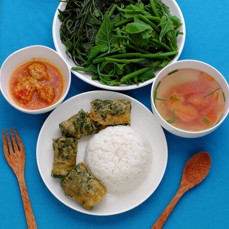 Top view Vietnamese meal lunch with boiled vegetables, tofu cheese, tomato soup, fried egg with mugwort, homemade vegan food for vegetarian on blue background Stock Photo