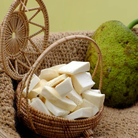 Close up raw material food from breadfruit cut in pieces in handmade bamboo basket on yellow background Stok Fotoğraf