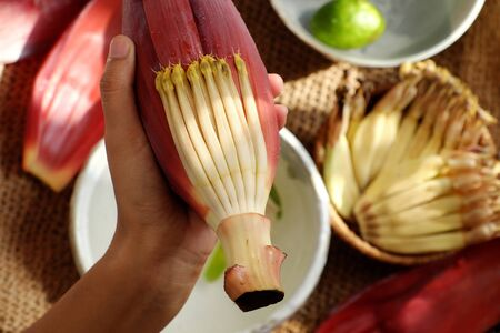 Top view prepare ingredients for vegan food  from banana flower, woman hand take young bananas, soaked in lemon water, this blossom can make many vegetarian dish, healthy eating with fiber Stock Photo
