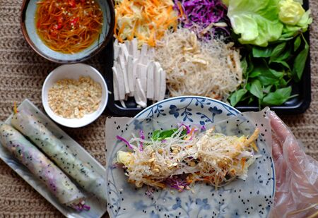 Top view people hand making vegan rice paper rolls, Vietnamese spring rolls by let ingredient as carrot, violet cabbage, sausage, vermicelli, tofu, salad, herbs into rice paper and rolling
