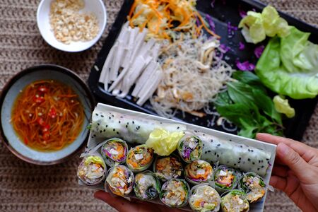 Close up sliced vegan rice paper rolls on Vietnamese spring roll ingredient background, colorful vegetables make vegetarian dish that healthy and delicious