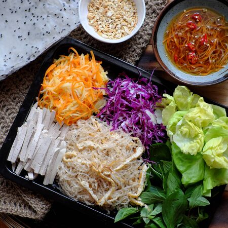 Top view ingredient food for fresh vegan rice paper rolls, a popular Vietnamese eating that healthy eating with colorful vegetables as carrot, violet cabbage, sausage, vermicelli, tofu, salad, herbs