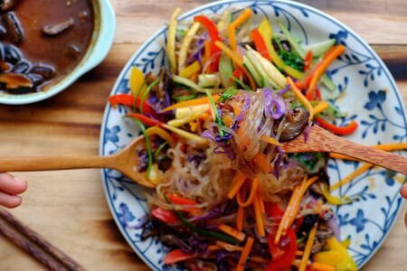Top view colorful plate of food, vegan mixed vermicelli with vegetables, red, yellow bell pepper, purple cabbage, coriander, cucumber, carrot with mushroom sauce, vegetarian dish on wooden background Stock Photo - 133195222