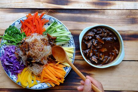 Top view colorful plate of food, vegan mixed vermicelli with vegetables, red, yellow bell pepper, purple cabbage, coriander, cucumber, carrot with mushroom sauce, vegetarian dish on wooden background