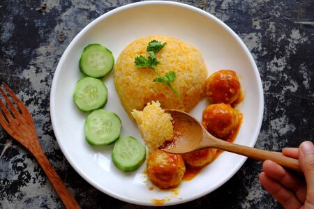 Top view people eating Vietnamese vegan rice dish with meatballs from tofu ball with tomato sauce, cucumber for vegetarian lunch meal, homemade delicious and safe, healthy food from Vegetal diet Stock Photo - 133195228