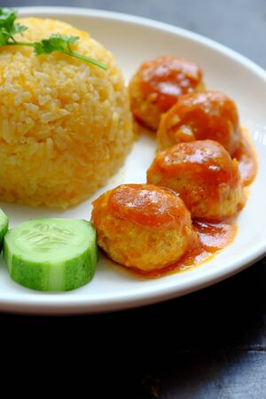 Close up Vietnamese vegan rice dish with meatballs from tofu ball with tomato sauce, cucumber for vegetarian lunch meal, homemade delicious and safe, healthy food from Vegetal diet