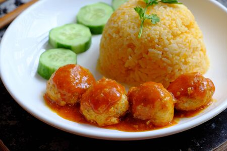 Close up Vietnamese vegan rice dish with meatballs from tofu ball with tomato sauce, cucumber for vegetarian lunch meal, homemade delicious and safe, healthy food from Vegetal diet Reklamní fotografie
