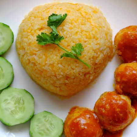 Top view Vietnamese vegan rice dish with meatballs from tofu ball with tomato sauce, cucumber for vegetarian lunch meal, homemade delicious and safe, healthy food from Vegetal diet Stock Photo - 133195232