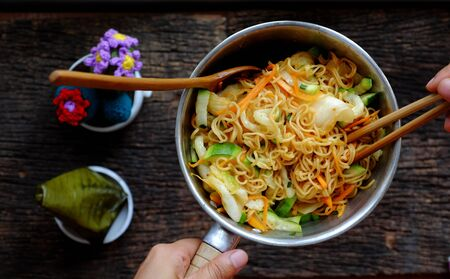 Top view close up human hand mix yellow dry instant noodles with vegetables for quick vegan breakfast on dark wooden background