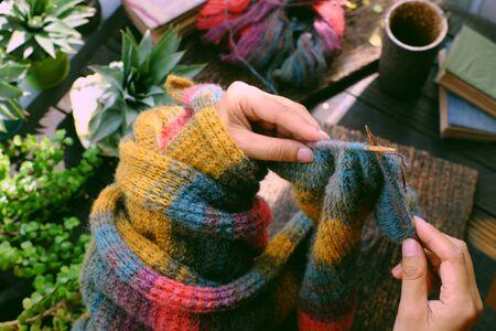 Frau von oben, die auf dem Balkon zu Hause sitzt, ein Stück Papier mit einer Schreibnachricht in der Hand halten, einen bunten Wollschal für ein bedeutungsvolles handgemachtes Wintergeschenk stricken, wenn der Winter kommt.