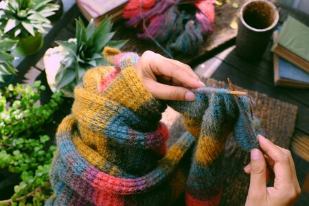 Top view woman sitting at home balcony, hand hold piece of paper with writing message, knit colorful wool scarf for meaningful handmade winter gift when wintertime come.