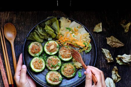 Vietnamese homemade vegetarian eating on black plate on wooden background, grilled vegetables with slice of winter melon stuff with tofu and carrot, delicious vegan meal that frugal, healthy. Stock Photo - 133026440