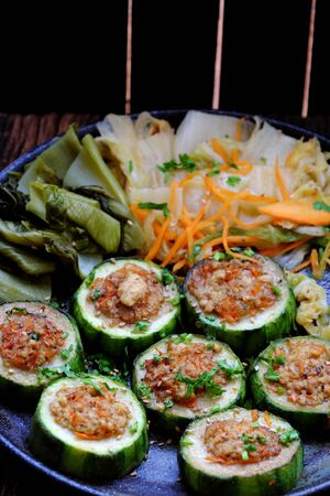 Vietnamese homemade vegetarian eating on black plate on wooden background, grilled vegetables with slice of winter melon stuff with tofu and carrot, delicious vegan meal that frugal, healthy.
