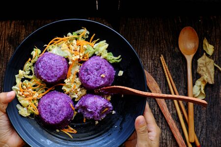 Vietnamese homemade vegetarian eating on black plate, violet rice dish with vegetables, delicious vegan meal that frugal, healthy
