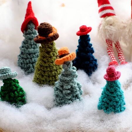 Group of green Christmas tree wear colorful hat crochet from yarn to make handmade ornament for winter holiday at wintertime on white background, cute concept for home decor or seasonal gift.