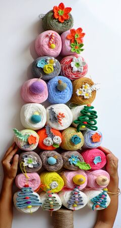 Impression ideas Christmas decoration by group of colorful ball of yarn making simple Christmas tree with ornaments to decor as flower, leaf, top view decorative tree for winter holiday so amazing