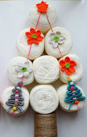 Winter seasonal ideas concept on white background, making simple Christmas tree from group of white ball of yarn with craft colorful ornaments are crochet product, amazing artwork for decoration noel