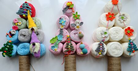 Winter seasonal ideas concept on white background, making simple Christmas tree from group ball of yarn with craft colorful ornaments are crochet product, amazing artwork for decoration noel