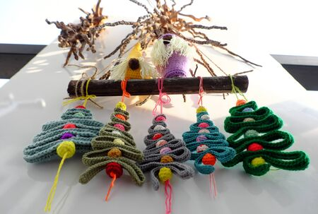 Amazing simple decoration home on white wall for winter seasonal with crochet handmade product, gnome stand on dry bamboo, group of ribbon Christmas tree with colorful baubles, ornaments hang on wall