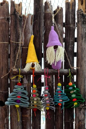 Amazing simple decoration home on wall for winter seasonal with crochet handmade product, gnome stand with group of ribbon Christmas tree and colorful baubles, ornaments hang on bamboo background
