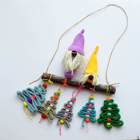 Amazing simple decoration home, ornaments winter seasonal with crochet handmade product, gnome stand on dry bamboo, group of ribbon Christmas tree with colorful baubles on white background