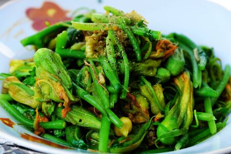 Plate of green pumpkin flower buds fried with cooking oil for vegetarian meal, nutrition, delicious and healthy non meat eating from vegetables