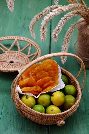 Vietnamese traditional food for tet holiday, close up yellow round kumquat jam and raw material in basket on green wooden background, homemade sweet snack food from fruits for tea time in spring Imagens