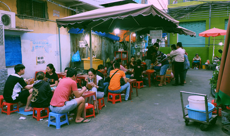 HO CHI MINH CITY, VIET NAM- NOV 15, 2019: Group of people also diners sit on plastic tables and chair outside pork offal restaurant to eat pha lau, a popular Vietnamese street food, Vietnam