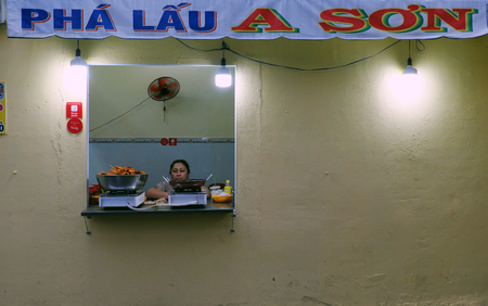 HO CHI MINH CITY, VIET NAM- NOV 15, 2019: Woman sit by window of pork offal restaurant, a Vietnamese street food, small food store with yellow wall at evening Editorial