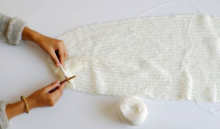 Top view simple concept for wintertime, woman hand with knitting needles to knit white scarf for handmade seasonal gift on white background, amazing gentles color