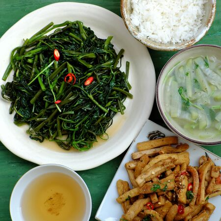 Top view simple vegan meal for daily family menu with fried tofu cook with sauce, fried water spinach and vegetables soup, bowl of rice, Vietnamese food for vegetarian healthy eating Imagens