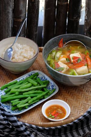 Vietnamese daily meal for lunch, vegan food menu with boiled peas, bowl of okra, tomato, tofu soup and rice on tray, ready to eat Imagens