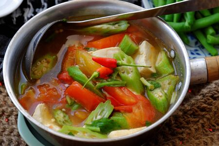 Vietnamese vegan soup in pot from vegetables are okra, tofu, tomato, Eryngium, simple daily menu that healthy, nutrition and delicious