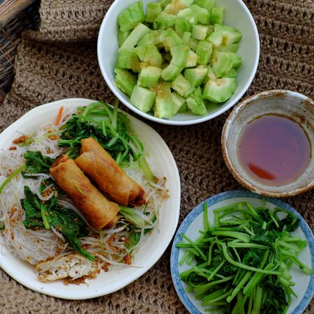 High view Vietnamese vegetarian food for breakfast, close up plate of rice noodle with fried spring roll and vegetables for vegan meal, simple but delicious and healthy food