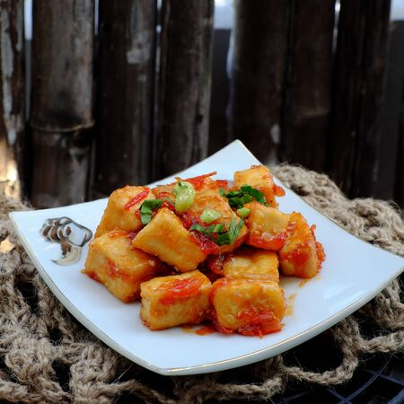 Close up simple vegan meal for daily family menu with fried tofu cook with tomato sauce, healthy, nutrition and delicious Vietnamese food