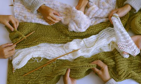 Amazing scene from indoor top view, group of woman hand with knitting needles to knit wool white and mossy green scarf on white background for winter handmade gift, funny scene for winter concept