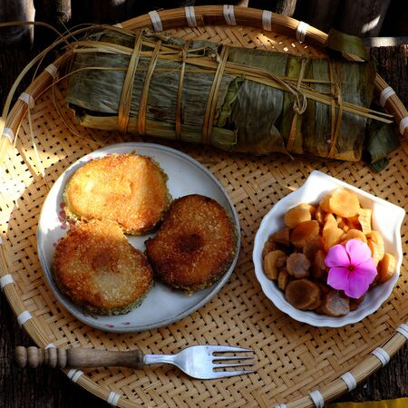 Close up of Vietnamese traditional food for Tet holidays, delicious fried glutinous rice cake on plate on wooden background for breakfast