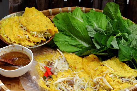 Vietnamese food for vegetarian, homemade vegan pancakes make from rice flour, stuff with chopped chayotr, abalone mushrooms and sprout, eat with herbal vegetables