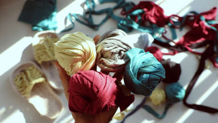 Close up from top view colorful scene in sunlight morning, woman hand hold group ball of yarn from recycle old t shirt on white background, fun leisure with homemade reuse by cut clothes in yarns