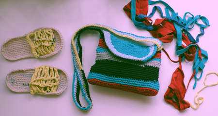 Close up from top view woman hand hold colorful handmade bag from recycle old t shirt on white background, reuse clothes by cut in yarns then crochet to make diy product in leisure activity 版權商用圖片